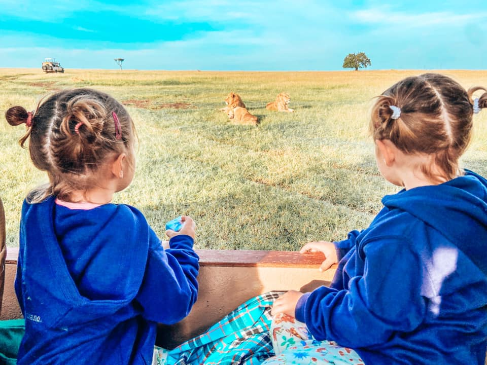 two girls sitting in the safari jeep watching lions sleeping in the grass