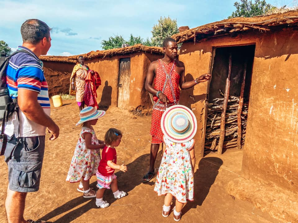daddy and children listening to a Maasai man standing outside a mud hut
