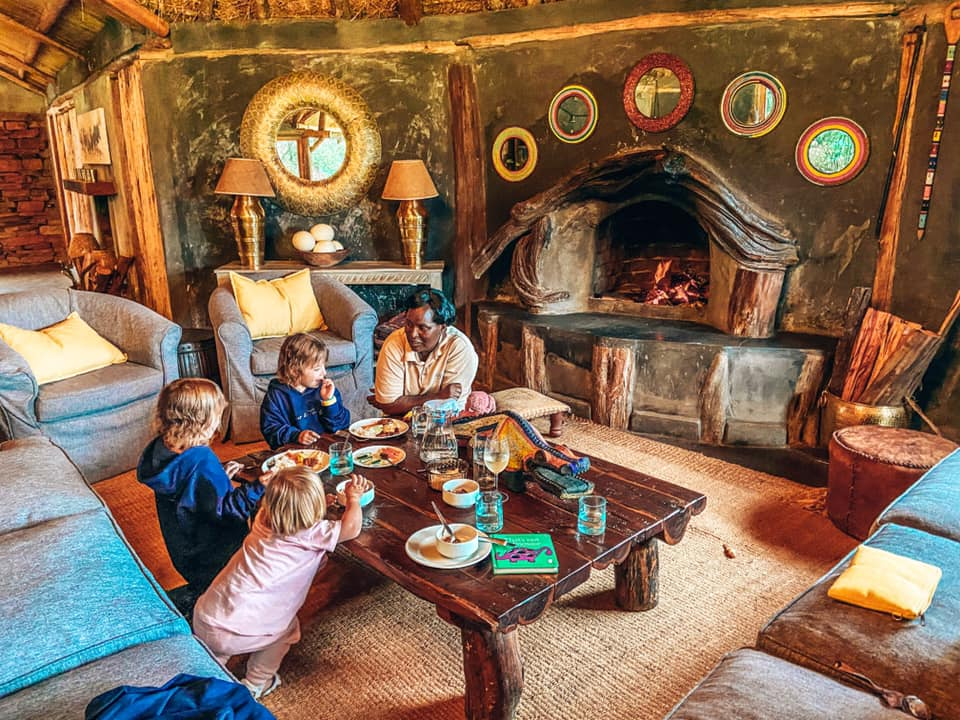 family eating at a small table sat on the floor in the House in the Wild lunch in the main house
