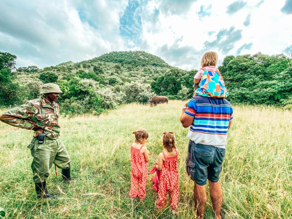 father and children watching a rhino from a distance alongside park ranger