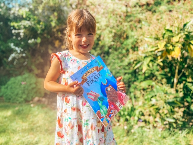 Little girl holding a personalised story book about pirates in the garden