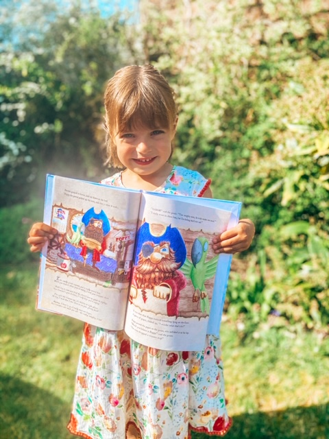 Little girl holding a page open showing the illustrations and her name in the personalised story book about pirates in the garden