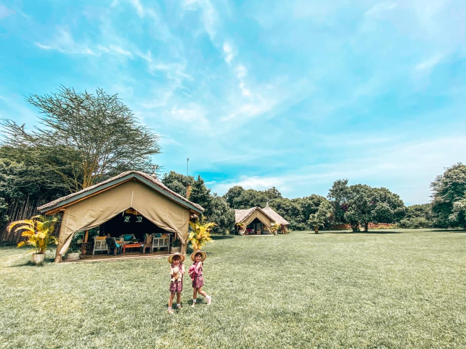 Children standing on the grass outside some luxury tents