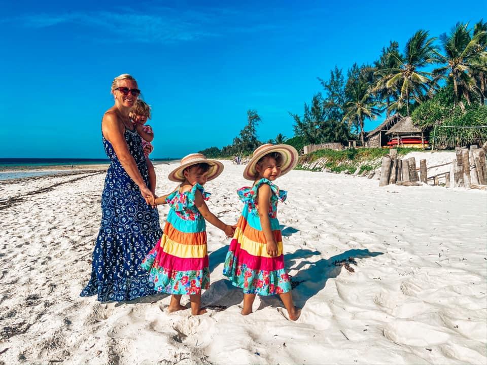 mummy and three children walking on the white sandy beach in Kenya