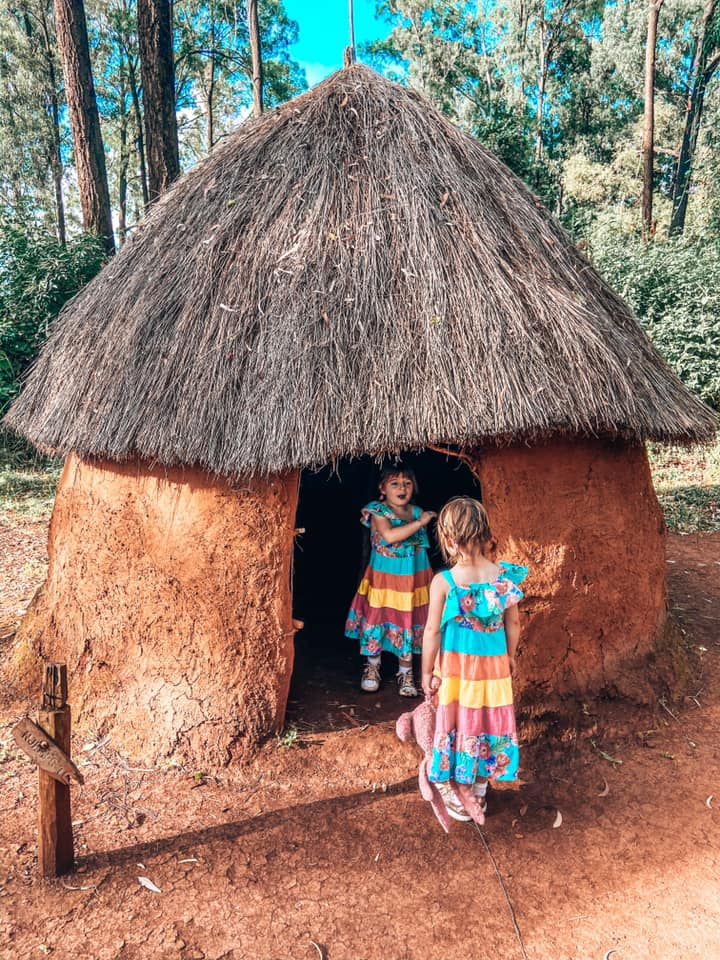 twins wearing multi coloured dresses in thatched hut
