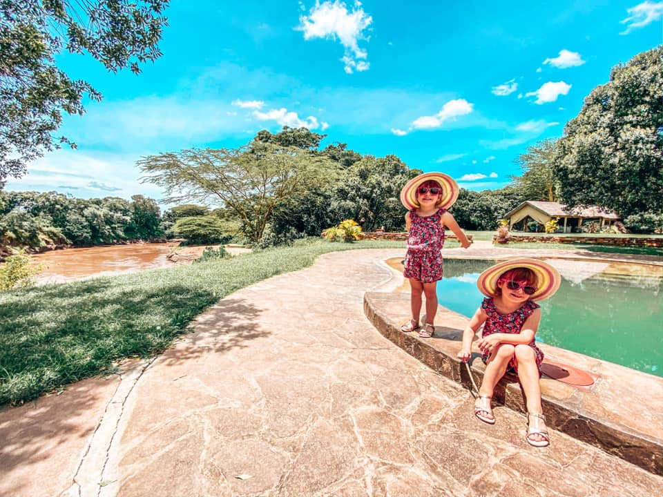 twins sat alongside a pool in House in the Wild at Maasai Mara