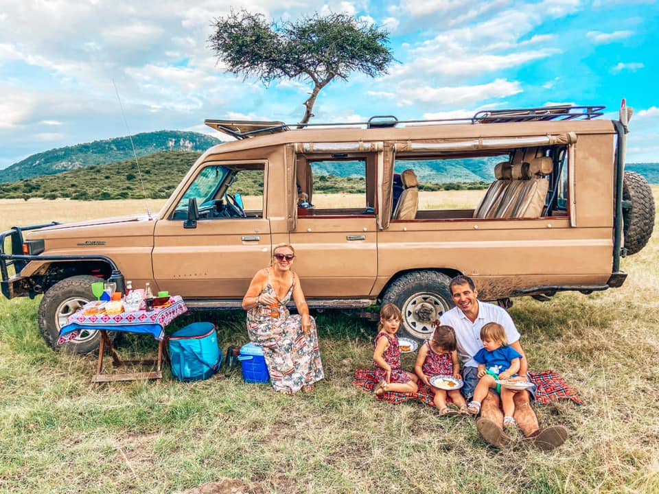family sat on blankets in front of safari jeep eating breakfast