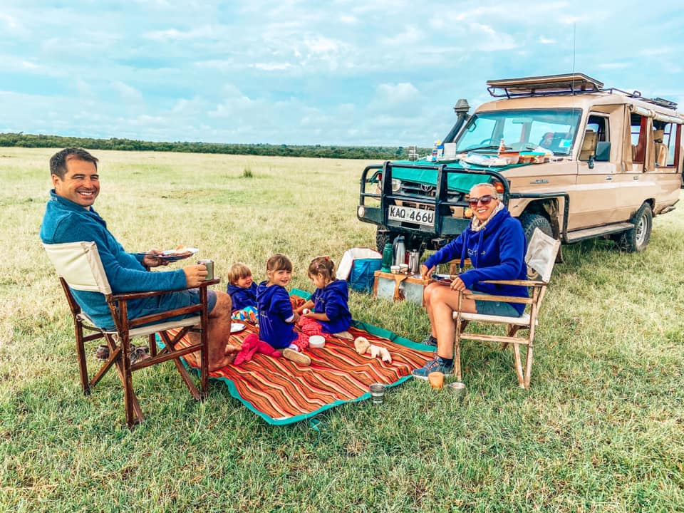 family sat on chairs and blanket Maasai Mara with Kids bush breakfast