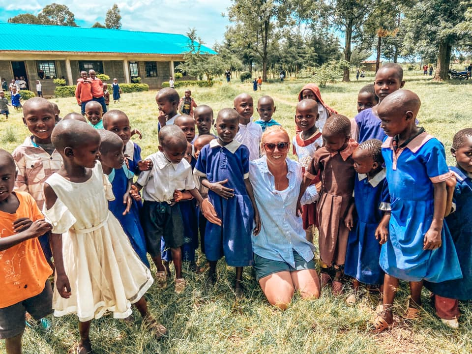 Anna hugging children from the local school and surrounded by children mainly wearing blue.