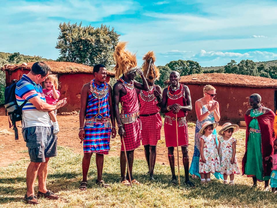 family surrounded by residents of Maasai Mara with Kids maasai dancers