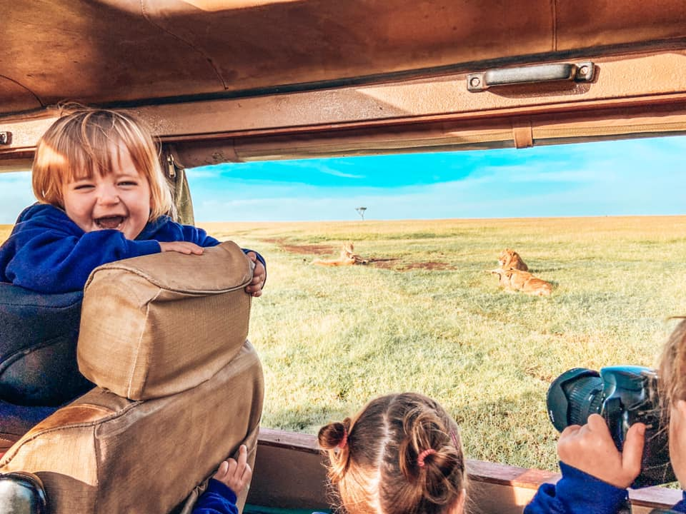 onboard a jeep on safari in Maasai Mara with Kids looking at lions