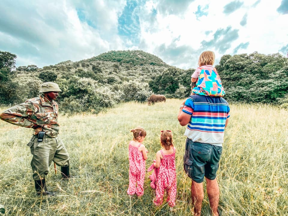 family with child on shoulders of father and two twins wearing pink jumpsuits along side safari ranger overlooking the rhino in and amongst knee high grass surrounded by trees