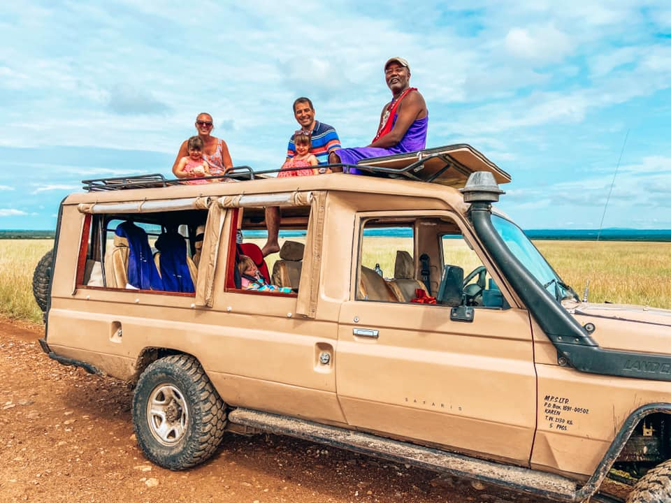 Maasai Mara safari jeep with Kids sat  on the roof