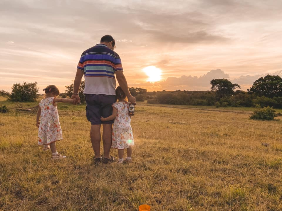 father holding hands of children on safari in Maasai Mara with Kids with the sun going down