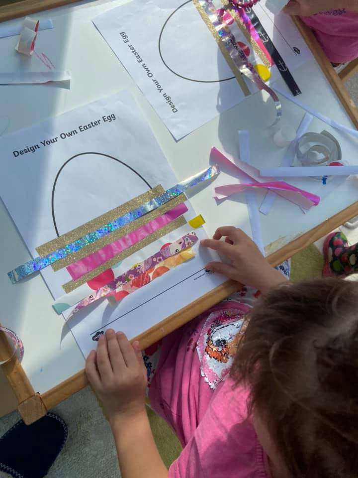 child sticking strips of paper onto an outline of an egg