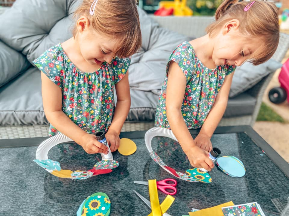twins sticking paper Easter eggs onto a paper plate with glue