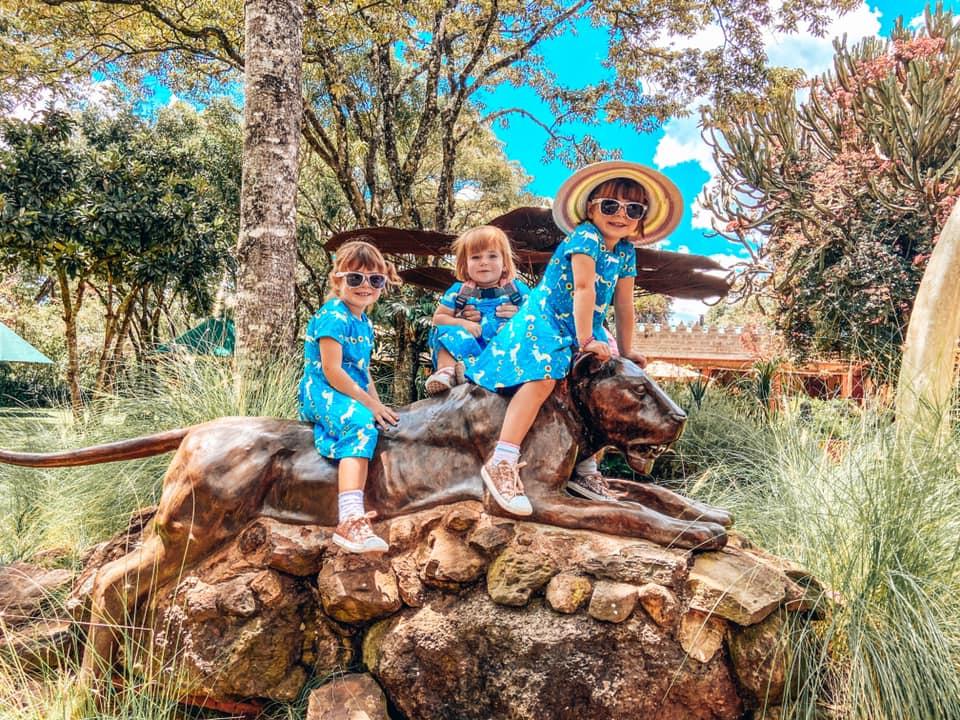 3 Girls all wearing blue dresses in Nairobi Mat Bronze sat on a sculpture of a cheetah
