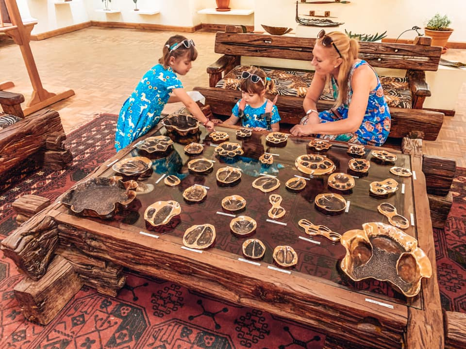 Nairobi with Kids Mat Bronze showroom with mum wearing blue dresses and touching display on table