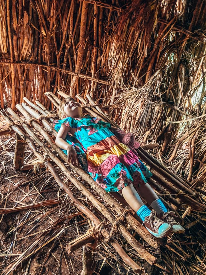 girl laid on a bed inside the thatched hut made of sticks