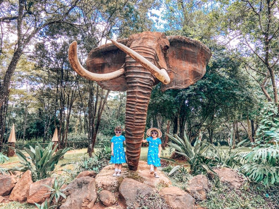 twins wearing sunglasses and a blue dress underneath the elephant sculpture in Matt Bronze