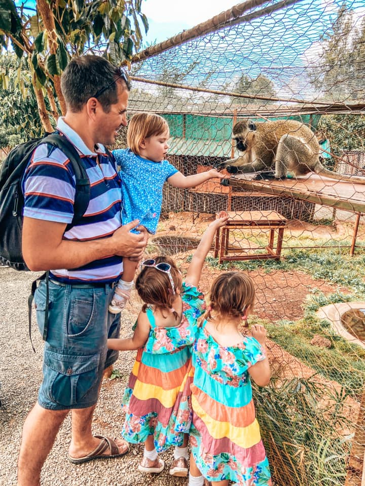 family father and three children feeding monkey at rescue centre