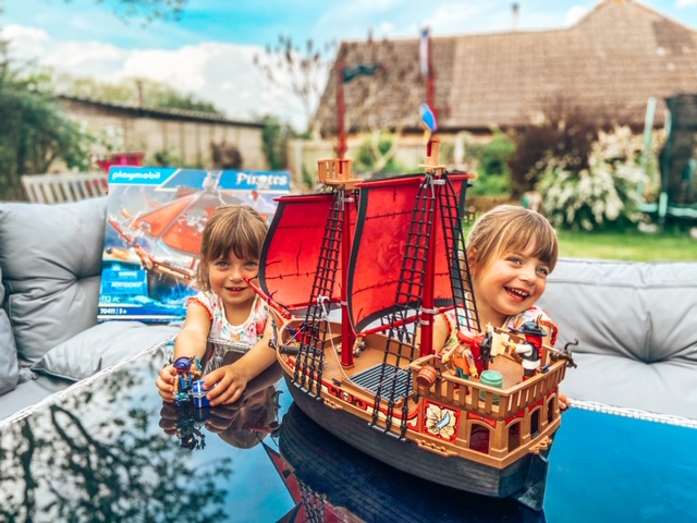 twins smiling in the garden with a Playmobil pirate ship which they have just build. The sails are read and the boar brown imitating wood.