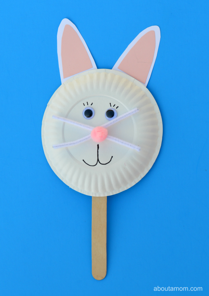 Easter bunny puppet made out of a white paper plate stuck onto a lolly stick
