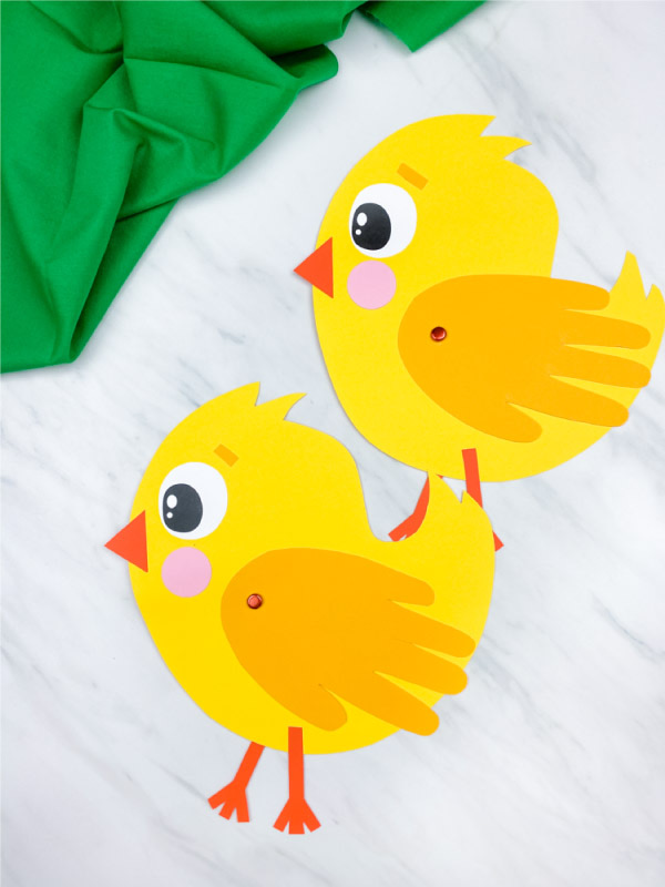 two paper yellow chicks with wings made out of cut out hand prints