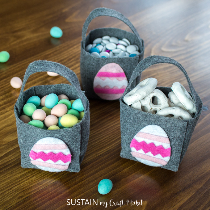 three felt Easter baskets with pink felt Easter eggs on the front filled with sweets