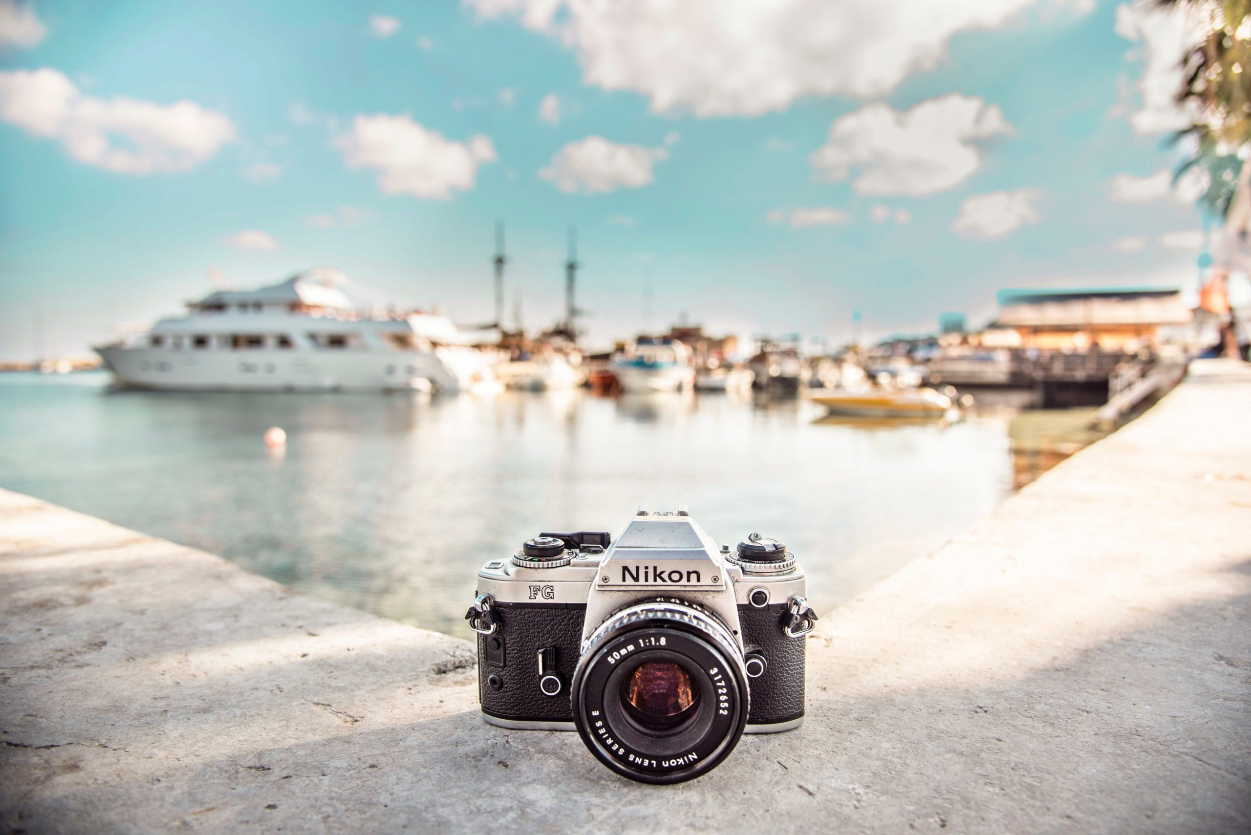 A camera sitting on a wall with the sea in the background filled with boats