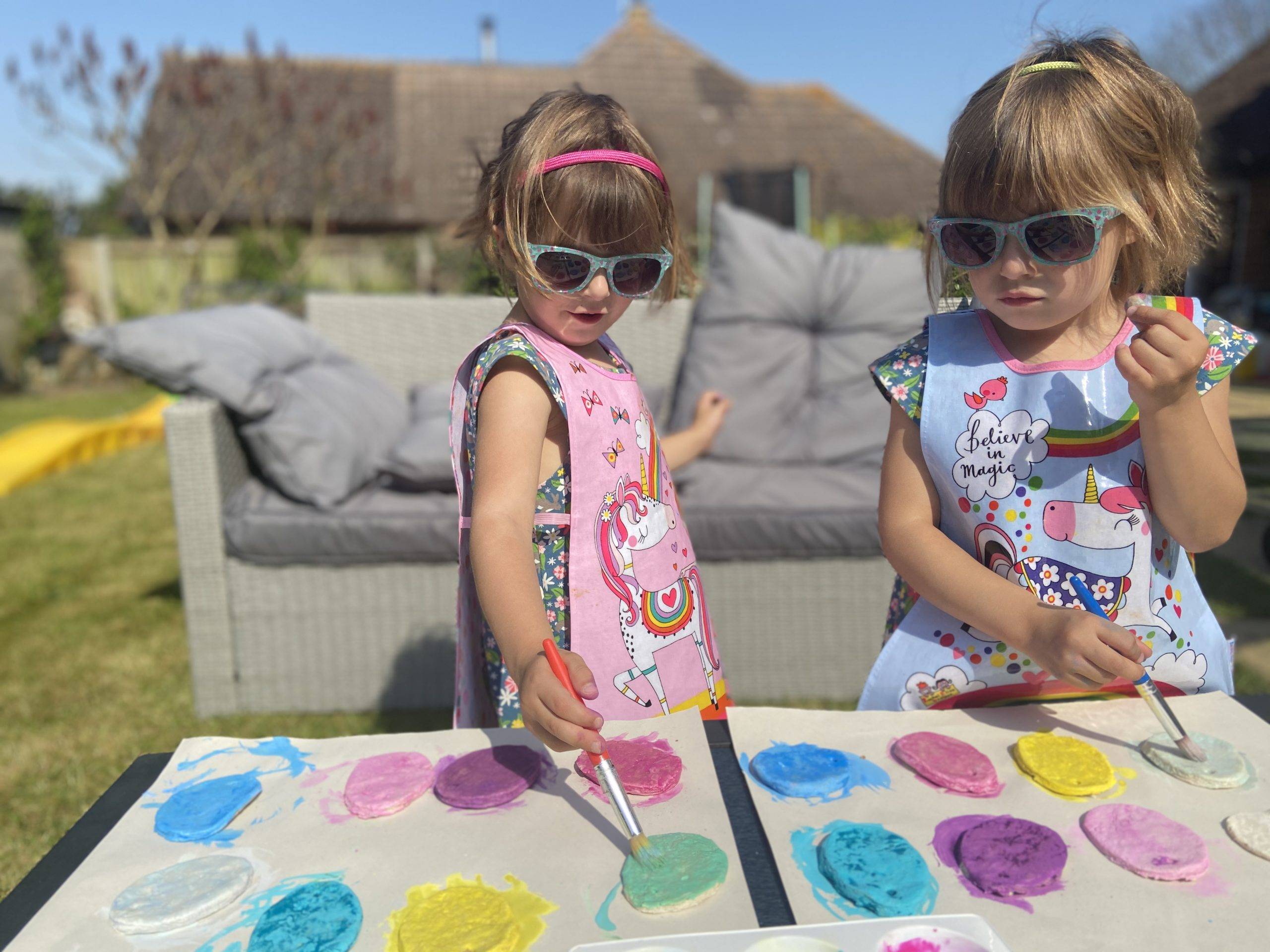 two girls outside in the garden wearing art aprons painting salt dough with a paintbrush