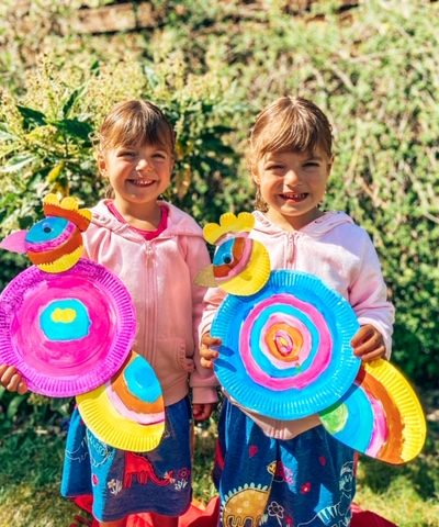 twin girls standing in the garden holding paper plate parrots they have made. They are rainbow colours