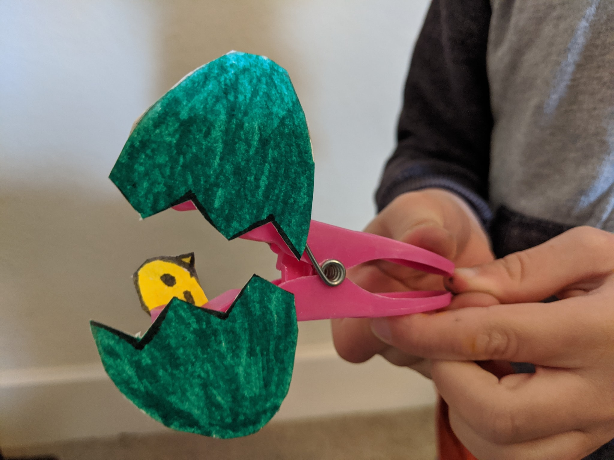 Easter craft on a peg. A hand is pinching the peg to split the chick egg open to reveal a chick