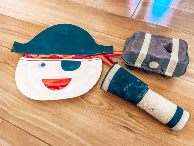 Three pirate crafts sitting on the table. A paper plate pirate, loo roll telescope and a treasure box made out go an egg box
