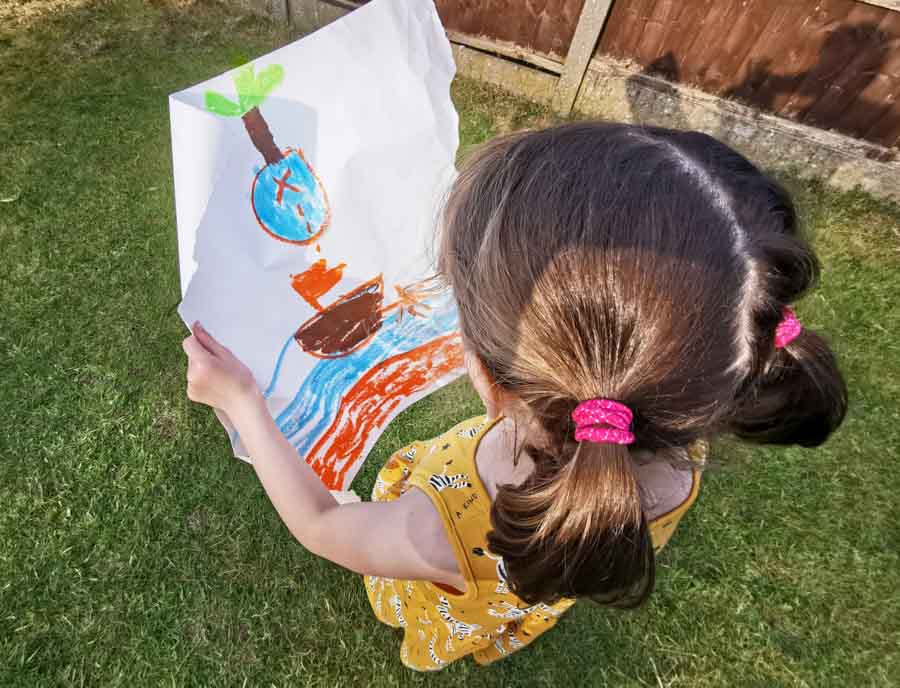 Little girl standing in the garden holding a map she has painted herself