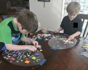 two boys sticking pieces of paper onto sticky backed plastic in the shape of an egg