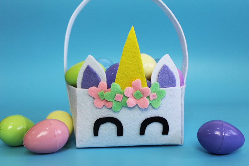 Unicorn Easter baskets with purple ears which is filled with plastic eggs