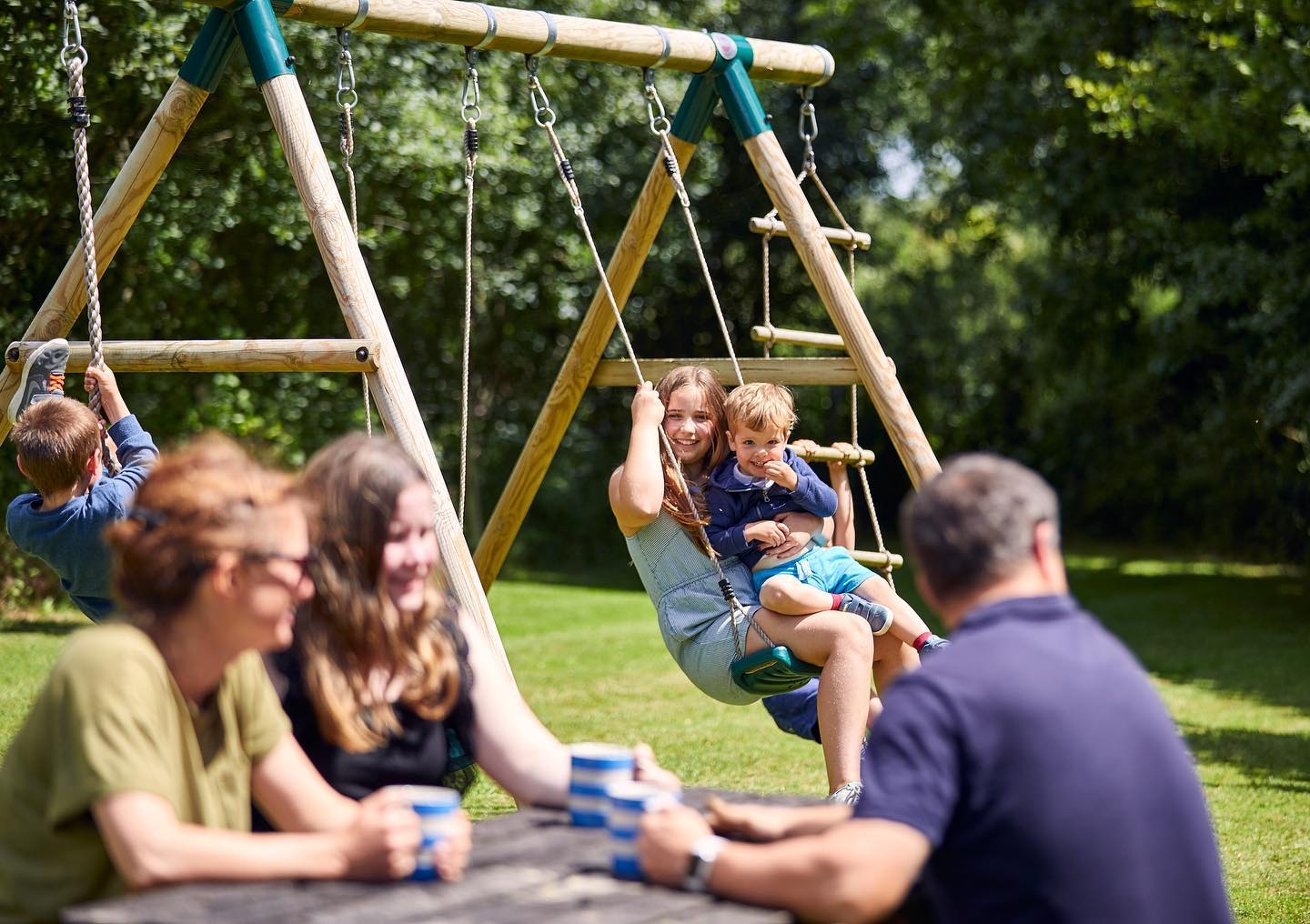 Family play area with adults drinking coffee and children playing on the swings
