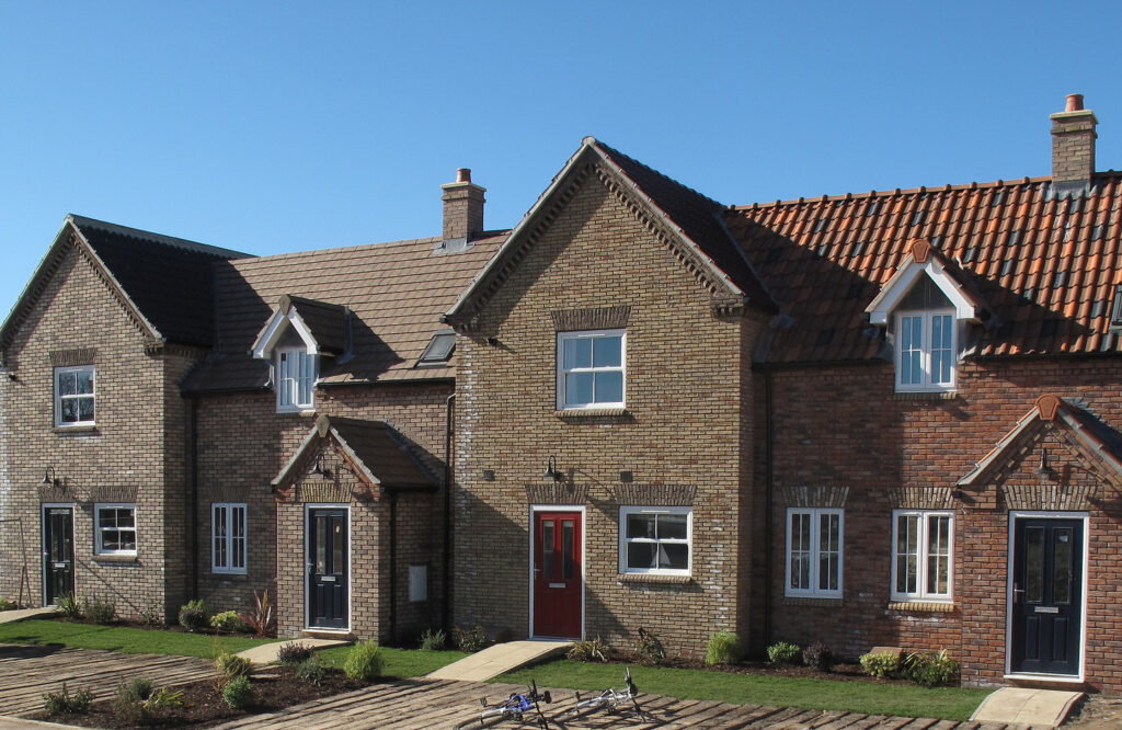 Brick terraced house with a red door and a small grass garden to the front with a small path leading to the front door