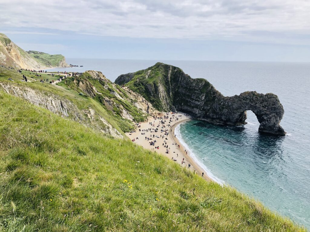 large hill rolling down to the beach with is full of visitors playing and walking along the coastal path
