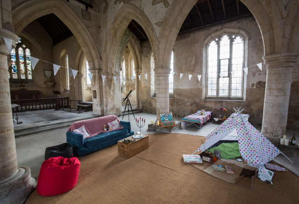 Inside of a church with sofas and beds set up as a house
