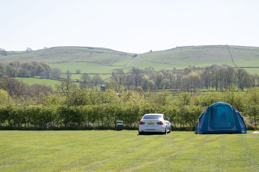 wide open field with a blue tent to the right and a white car next to it