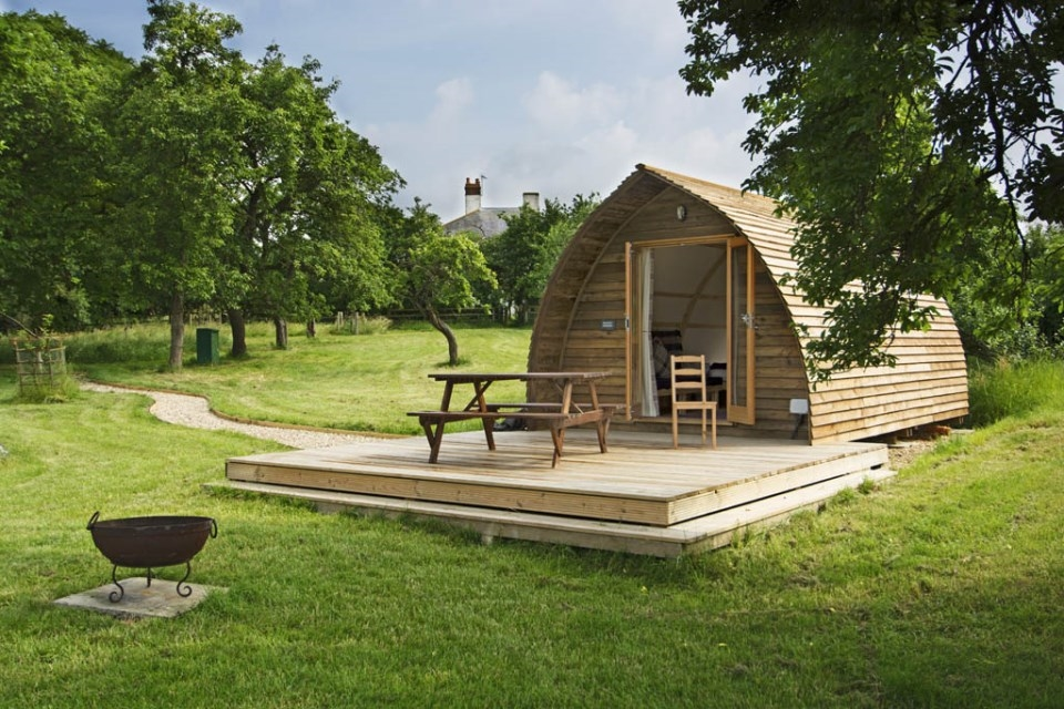 wooden wigwam on decking with a picnic table surrounded by grass and trees