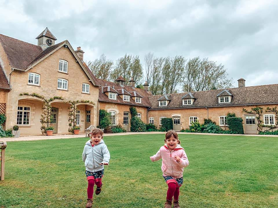 two children in a pink and blue hoodie running about on the grass, with cottages behind at Bruern Cottages. These are great UK Holidays with Toddlers