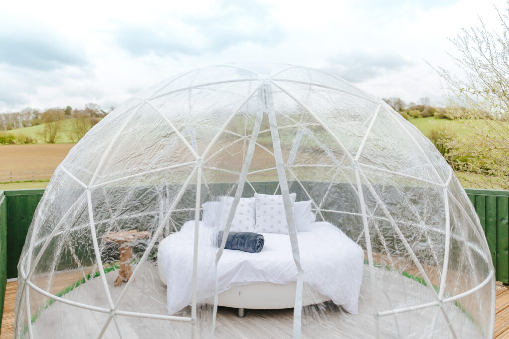 a glass dome with a bed inside fitted with white linen