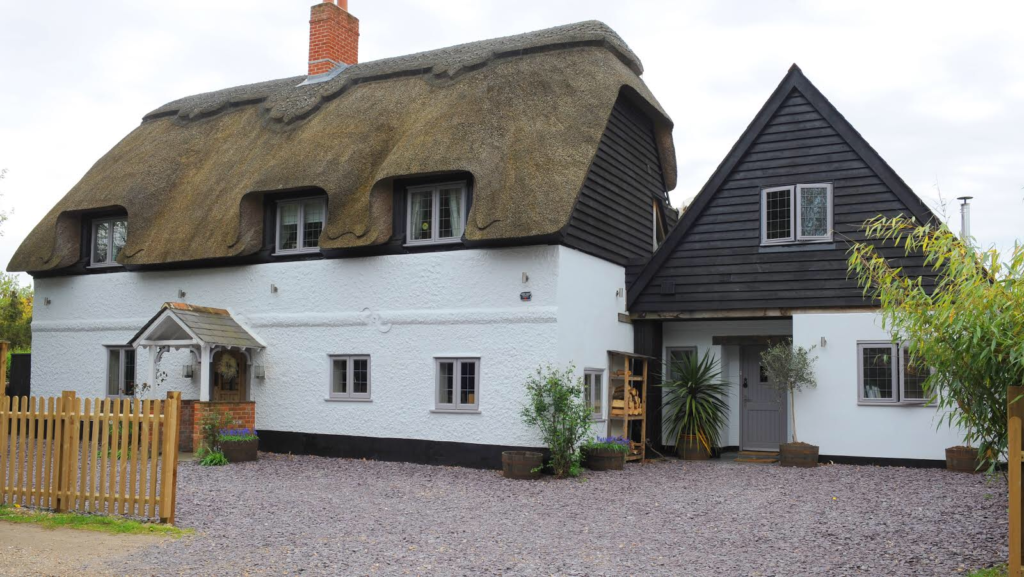 Dairy cottage is a white painted, thatched roof cottage with black wood clad at the top