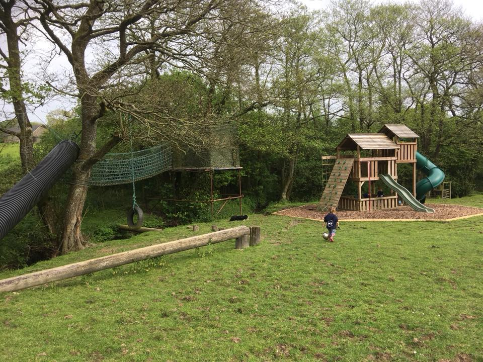 two children running down towards a huge adventure play area with a zip wire and tree house