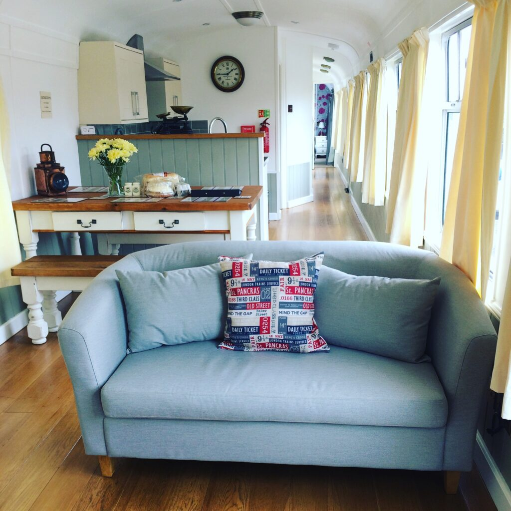Inside of a converted railway carriage with a blue sofa and cream table