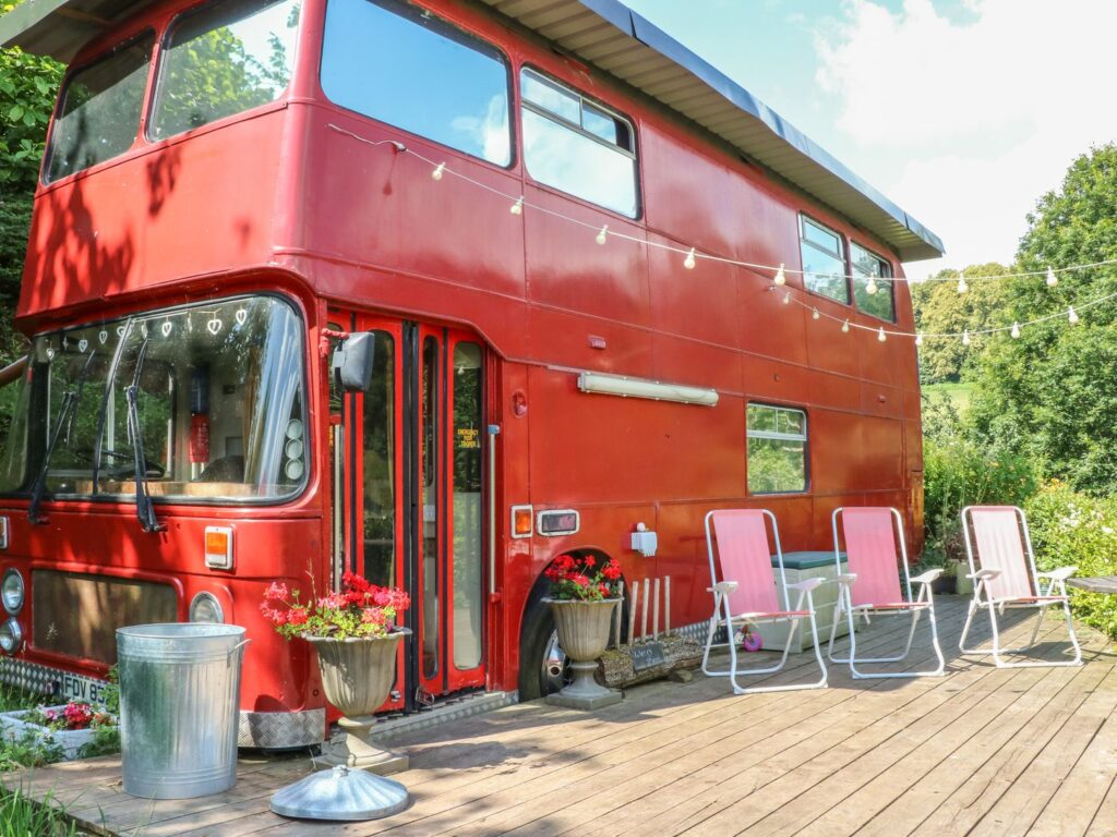 Red bus transformed in to holiday accommodation with decking out the front with tables and chairs and plant pots