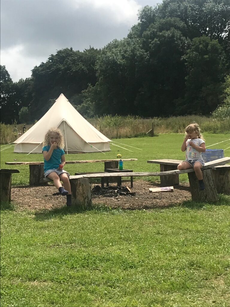 family campsite with tipi tents and two children sitting around the fire pit